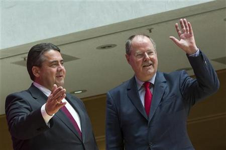 Former German Finance Minister and Social Democrat (SPD) member Peer Steinbrueck (R) waves to party members as he arrives at a news conference with SPD leader Sigmar Gabriel in Berlin, October 1, 2012. The main opposition's candidate for German chancellor, Peer Steinbrueck, laid out a gentler stance on Greece than Angela Merkel on Sunday, saying Athens needs more time to reform and should not be thrown out of the euro zone. REUTERS/Thomas Peter (GERMANY - Tags: POLITICS)