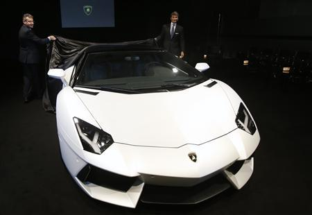 Chief Executive Officer of Automobili Lamborghini Stephan Winkelmann (R) and an employee unveil the new Lamborghini Aventador LP 700-4 Roadster in Singapore November 12, 2012. REUTERS/Edgar Su