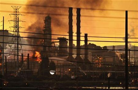 Firefighters douse a flame at the Chevron oil refinery in in Richmond, California August 6, 2012. A fire struck the core of Chevron Corp's large Richmond refinery on Monday evening, sending flames and a column of smoke into the air and prompting authorities to order nearby residents indoors. The fire, which authorities said was still blazing more than two and a half hours after it erupted, hit the sole crude unit at the 245,000 barrel per day (bpd) plant, which accounts for one-eighth of the state's refining capacity. REUTERS/Josh Edelson (UNITED STATES - Tags: DISASTER ENERGY ENVIRONMENT BUSINESS)