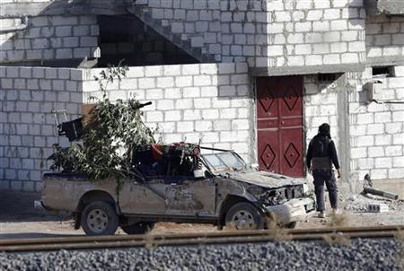 A Free Syrian Army fighter walks next to a truck in the Syrian town of Ras al-Ain, as seen from the Turkish border town of Ceylanpinar, Sanliurfa province November 12, 2012. A Syrian warplane bombed the rebel-held town of Ras al-Ain on Monday, just metres from the Turkish frontier, sending scores of civilians fleeing for safety into Turkey. Helicopters also strafed targets near the town, which fell to rebels on Thursday during an advance into Syria's mixed Arab and Kurdish northeast. REUTERS/Murad Sezer (TURKEY - Tags: POLITICS CONFLICT)