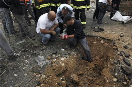 Israeli police survey the scene after a rocket, fired by Palestinian militants in Gaza, landed in the southern town of Netivot November 12, 2012. REUTERS/Ammar Awad