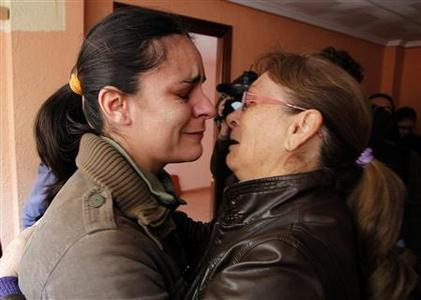 Crying Engracia Lucena (L) is hugged by a neighbour as she waits for the judicial comission to carry out the later suspended eviction from her home in Valencia, November 12, 2012. REUTERS/Heino Kalis