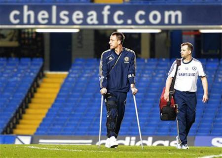 Chelsea's injured captain John Terry walks across the pitch following their English Premier League soccer match against Liverpool at Stamford Bridge Stadium in London, November 11, 2012. REUTERS/Russell Cheyne