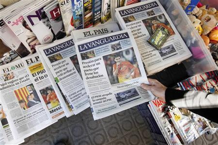 A person grabs a copy of the newspaper La Vanguardia written in Spanish placed next to a copy written in Catalan at Plaza de Catalunya in central Barcelona November 12, 2012. Barcelona-based newspaper La Vanguardia, which has the fourth highest circulation in Spain, started printing a Catalan edition last year. REUTERS/Gustau Nacarino