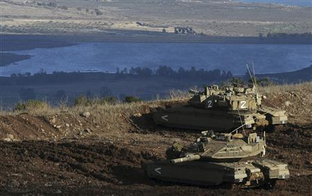 Israeli tanks stand in position overlooking a Syrian village from the Israeli-occupied Golan Heights November 12, 2012. Israel's army fired tank shells into Syria on Monday and scored ''direct hits'' in response to a Syrian mortar shell that struck the Israeli-occupied Golan Heights, the Israeli military said in a statement. REUTERS/Avihu Shapira