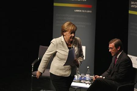 German Chancellor Angela Merkel (L) walks past Portugal Prime Minister Pedro Passos Coelho during a meeting with Portuguese-German businessmen at Belem Cultural Center in Lisbon November 12, 2012. REUTERS/Rafael Marchante