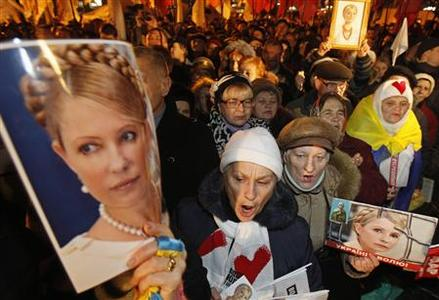 Supporters of opposition parties attend a protest rally, holding portraits of jailed former prime minister and opposition leader Yulia Tymoshenko, in front of Ukraine's central electoral commission in Kiev November 12, 2012. REUTERS/Gleb Garanich