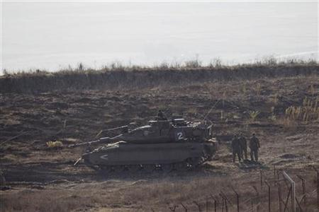 Israeli soldiers stand next to a tank close to the ceasefire line between Israel and Syria, near Alonei Habashan on the Israeli occupied Golan Heights November 7, 2012. REUTERS/Baz Ratner