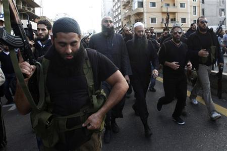 Armed supporters of Lebanon's Sunni Muslim Salafist leader Ahmad al-Assir (front row 3rd R) escort him and Lebanese singer Fadel Shaker (front row 2nd R) during the funeral of two of al-Assir's supporters, who died during Sunday's fighting with supporters of Lebanon's Hezbollah, in Sidon, southern Lebanon November 12, 2012. REUTERS/Ali Hashisho