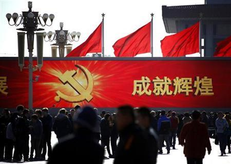 People walk in front of a large screen displaying propaganda slogans on Beijing's Tiananmen Square November 12, 2012. REUTERS/David Gray