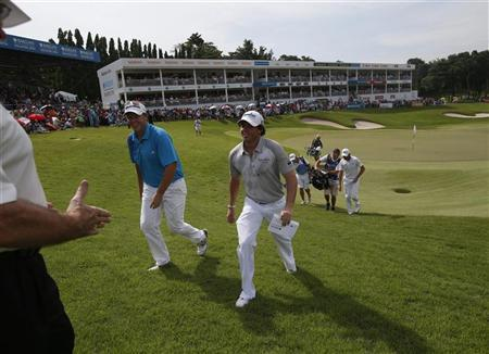 Rory McIlroy of Northern Ireland is congratulated by officials after he finished the final round of the Barclays Singapore Open golf tournament in Sentosa November 11, 2012. REUTERS/Edgar Su