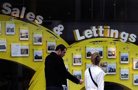 A couple pass the window of an estate agent in south London April 29, 2010. REUTERS/Toby Melville