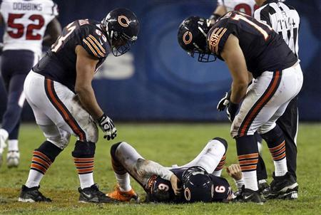 Chicago Bears quarterback Jay Cutler (6) lies on the field after being hit late on a play by the Houston Texans with his teammates over him during the first half of their NFL football game at Soldier Field in Chicago, November 11, 2012. Cutler didn't play in the second half. REUTERS/Jeff Haynes
