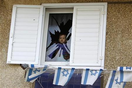 A baby is seen at a broken window after a rocket fired by Palestinian militants in Gaza hit a house in the southern town of Netivot November 12, 2012. The Palestinian rocket fired from the Gaza Strip struck the house in southern Israel on Monday, causing damage but no injuries, and Israeli officials quickly warned of a tough response to the latest surge in violence. REUTERS/Amir Cohen (ISRAEL - Tags: POLITICS CIVIL UNREST)