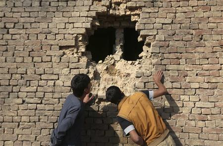 Afghan men look at a hole in the wall of a house caused by a rocket attack in Kabul November 13, 2012. REUTERS/Omar Sobhani