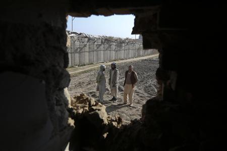 Afghan men are seen through a hole in the wall of a house caused by a rocket attack in Kabul November 13, 2012. A rocket landed near the Afghan intelligence agency in Kabul and two others struck near the airport highway and a private television station, security officials said. REUTERS/Omar Sobhani