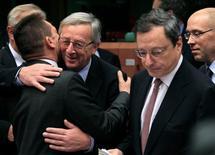 Los prestamistas internacionales de Grecia acordaron el lunes dar al país dos años más para que realice los recortes de gastos que se le exigen, pero la zona euro y el FMI discreparon sobre las metas a largo plazo para reducir la deuda del país heleno. En la imagen, el primer ministro de Luxemburgo y presidente del Eurogrupo, Jean-Claude Juncker (segundo por la izquierda) saluda al primer ministro de Finanzas, Yannis Stournaras (a la izquierda), junto al presidente del Banco Central Europeo (segundo por la derecha), Mario Draghi, en una reunión del Eurogrupo en Bruselas, el 12 de noviembre de 2012. REUTERS/Yves Herman