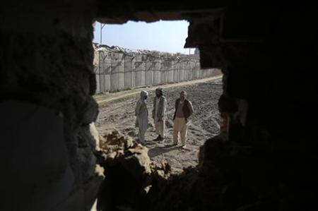 Afghan men are seen through a hole in the wall of a house caused by a rocket attack in Kabul November 13, 2012. REUTERS/Omar Sobhani (AFGHANISTAN - Tags: CONFLICT POLITICS)