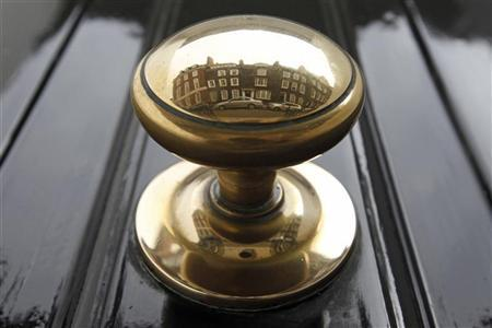 Houses are reflected in a door knob on a street in London March 13, 2012. REUTERS/Luke MacGregor