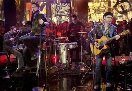 Australian rock band INXS (L-R) Andrew Farriss, J.D. Fortune (jumping), John Farriss, and Kirk Pengilly perform during a live television appearance on 'Much Music' in Toronto November 25, 2005. REUTERS/J.P. Moczulski/Files