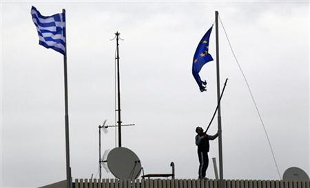 A man tries to replace a torn-off EU flag atop the Greek Ministry of Foreign Affairs in Athens February 8, 2012. Greek parties will try again on Wednesday to agree a reform deal in return for a new international rescue to avoid a chaotic default, after delays prompted some EU leaders to warn that the euro zone can live without Athens. REUTERS/Yannis Behrakis (GREECE - Tags: BUSINESS POLITICS)