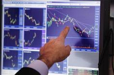 Un trader indica alcuni grafici con l'andamento dei mercati. REUTERS/Lucas Jackson