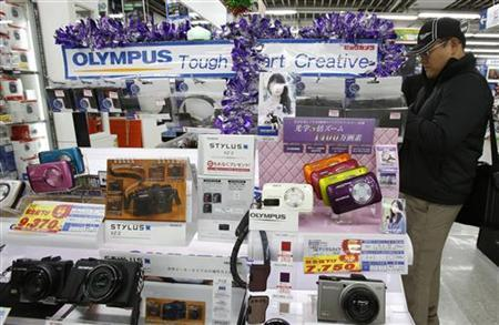 A man looks at Olympus Corp's products displayed at an electronics shop in Tokyo November 12, 2012. REUTERS/Yuriko Nakao