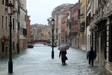 Tres personas murieron en Italia en medio de las fuertes lluvias cuando atravesaban un puente colapsado cerca de Grosseto, en el centro del país, según dijeron el martes las autoridades mientras las graves inundaciones continuaban en la Toscana. En la imagen, la gente camina por una calle inundada durante uan inundacion estacional en Venecia, el 11 de noviembre de 2012. REUTERS/Manuel Silvestri