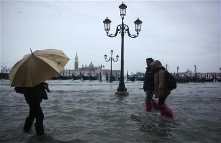 People walk through a flooded street during a period of seasonal high water in Venice November 11, 2012. REUTERS/Manuel Silvestri