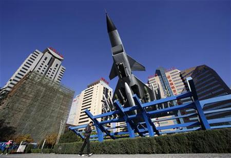 A man walks past a replica of a Chinese Jian-10 fighter jet outside the Aviation Industry Corporation of China (AVIC) headquarters building in Beijing October 30, 2012. REUTERS/Jason Lee