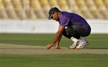 Mahendra Singh Dhoni inspects the pitch during a cricket practice session in Ahmedabad November 12, 2012. REUTERS/Amit Dave