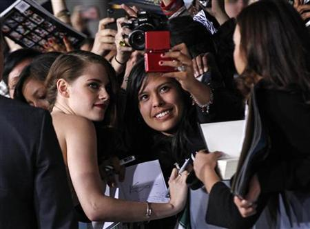 Cast member Kristen Stewart poses with a fan at the premiere of 'The Twilight Saga: Breaking Dawn - Part 2' in Los Angeles, California, November 12, 2012. The movie opens in the U.S. on November 16. REUTERS/Mario Anzuoni