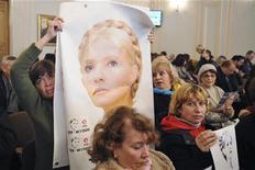 El segundo juicio de la encarcelada líder opositora Yulia Tymoshenko fue aplazado de nuevo el martes hasta el 23 de noviembre, porque la ex primera ministra, que está en huelga de hambre, no pudo asistir. En la imagen, varios seguidores de Tymoshenko con fotos suyas en un tribunal en Jarkiv el 13 de noviembre de 2012. REUTERS/Dmitry Neymyrok