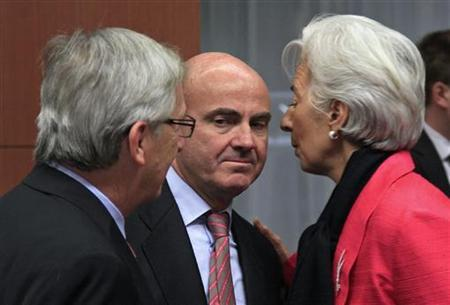 Spain's Economy Minister Luis de Guindos (C) is greeted by Luxembourg's Prime Minister and Eurogroup chairman Jean-Claude Juncker (L) and International Monetary Fund (IMF) Managing Director Christine Lagarde at a Eurogroup meeting in Brussels November 12, 2012. REUTERS/Yves Herman