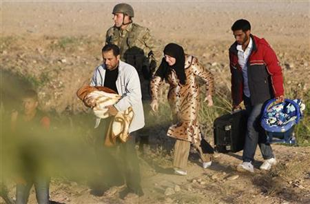 A Syrian family from the northern Syrian town of Ras al-Ain is escorted by a Turkish soldier after they crossed the border fences to flee Turkey in the Turkish border town of Ceylanpinar, Sanliurfa province November 12, 2012. REUTERS/Murad Sezer