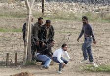Syrian refugees try to cross the border fence from the northern Syrian town of Ras al-Ain into Turkey during an air strike on Ras al-Ain, in the Turkish border town of Ceylanpinar, Sanliurfa province November 13, 2012. A Syrian warplane struck homes in the town of Ras al-Ain on Tuesday within sight of the Turkish border, pursuing an aerial bombardment to force out rebels, a Reuters witness and refugees said.The second day of jet strikes sent Syrians scurrying through the flimsy barbed-wire fence that divides Ras al-Ain from the Turkish settlement of Ceylanpinar, thick plumes of smoke rising above the town. REUTERS/Osman Orsal