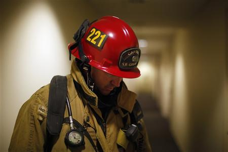 Firefighter Captain Tim Smith, 41, checks a building after its fire alarm sounded in San Bernardino, California September 11, 2012. The city of about 210,000, some 65 miles (104 km) east of Los Angeles, filed for bankruptcy on August 1, joining the Bay Area city of Stockton as a test case for whether financially troubled municipalities can shed bond payments and possibly pension obligations via bankruptcy court. Picture taken September 11, 2012. To match Special Report BERNARDINO/BANKRUPT REUTERS/Lucy Nicholson