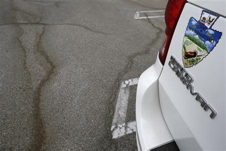Cracks in the road are seen next to a city vehicle in San Bernardino, California September 11, 2012. REUTERS/Lucy Nicholson