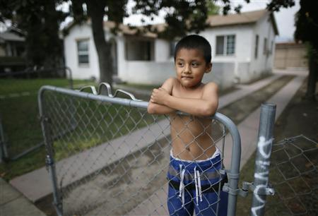 A boy leans on the gate in the home next door to where 21-year-old Angel Cortez was murdered in San Bernardino, California September 11, 2012. REUTERS/Lucy Nicholson