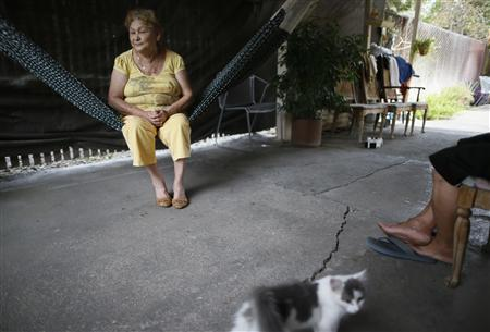 Maria Arias (L), 73, and her husband Manuel Arias, 73, sit in their driveway opposite the home where 21-year-old Angel Cortez was murdered in San Bernardino, California September 11, 2012. REUTERS/Lucy Nicholson