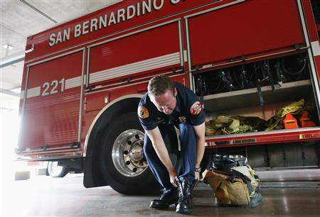 Firefighter Captain Tim Smith, 41, puts on his boots to answer a call in San Bernardino, California September 11, 2012. REUTERS/Lucy Nicholson