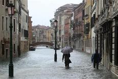 Pessoas caminham em rua inundada durante período de alta das águas, em Veneza. Três pessoas morreram quando o carro em que estavam caiu de uma ponte que desabou em consequência de fortes chuvas perto da cidade de Grossetto, na região central da Itália. 11/11/2012 REUTERS/Manuel Silvestri
