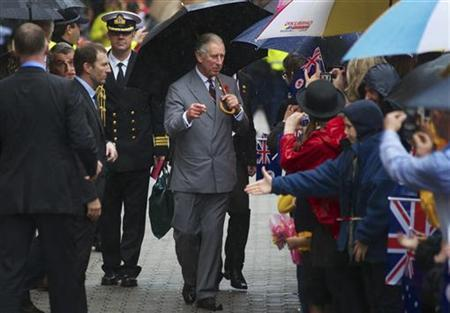 Britain's Prince Charles takes shelter under an umbrella as he meets well wishers in the popular shopping area Salamanca Place in Hobart November 8, 2012. REUTERS/Matt Newton