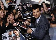 """Membro do elenco, Taylor Lautner dá autógrafos na premier do filme """"Amanhecer - Parte 2"""", em Los Angeles, Califórnia. Milhares de fãs alucinados se aglomeraram na noite de segunda-feira em torno do tapete preto pelo qual os astros de """"Crepúsculo"""" passaram na pré-estreia mundial do último episódio da série, """"Amanhecer - Parte 2"""". 12/11/2012 REUTERS/Mario Anzuoni"""