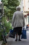 An elderly woman carries bags as she walks on a street in Berlin, September 3, 2012. REUTERS/Thomas Peter (GERMANY - Tags: POLITICS SOCIETY)