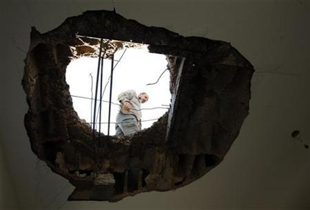 A Palestinian is seen through a hole in the ceiling of a house, caused by what Palestinians said was an Israeli missile, at Jabalya refugee camp in the northern Gaza Strip November 13, 2012. REUTERS/Ahmed Zakot