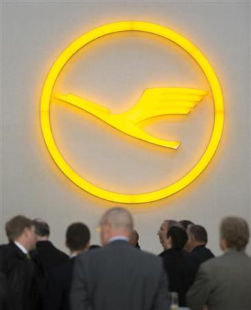 People stand under the logo of the Lufthansa carrier during the inauguration of the A330-200 passenger plane flight simulator at the Lufthansa Flight Training (LFT) centre in Berlin, November 1, 2012. REUTERS/Thomas Peter (GERMANY - Tags: TRANSPORT BUSINESS LOGO)