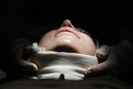 A woman lies on an operating table during a facelift surgery at a private plastic surgery clinic in Budapest, March 1, 2012. REUTERS/Bernadett Szabo/Files