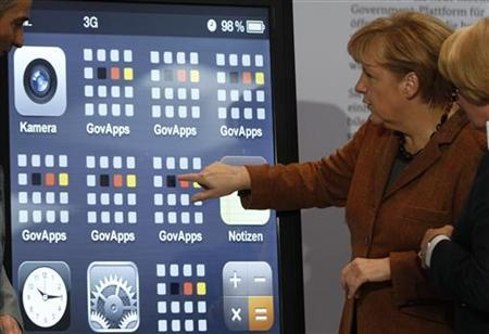 German Chancellor Angela Merkel points at a large smartphone picture during the seventh national IT-Summit in Essen November 13, 2012. The German government presented a information platform for smartphones. REUTERS/Ina Fassbender (GERMANY - Tags: POLITICS SCIENCE TECHNOLOGY)