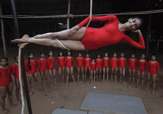 A girl practices a Mallakhamb pose while suspended from a rope at the Shree Samartha Vyayam Mandir in Mumbai, October 19, 2012. Mallakhamb is an ancient Indian sport which originated as a complementary exercise for wrestling, but is now practiced as a sport in itself. The name is a combination of the words 'malla', which means athlete or strong man, and 'khamba', which means pole. Athletes perform a variety of yogic and gymnastic poses while suspended from a rope or on a pole. Practitioners say that the sport not only develops a healthy and strong body, but also strengthens willpower and helps compose the mind. REUTERS/Vivek Prakash